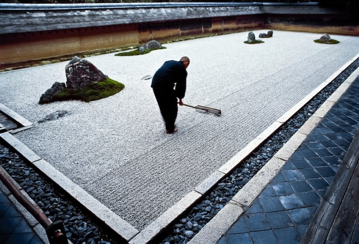 Apprentice monk rakes the garden at Ryoanji, a Zen temple in Kyoto.  The rock and sand garden embodies Japanese aesthetics-nature at its simplest, art at  its most refined. Japan